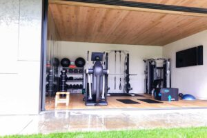 home gym with open floor to ceiling sliding door featuring tv, strength exercise equipment, technogym cardio, yoga mats, plyo boxes, gym storage and free weights