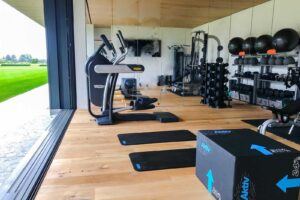 home gym in hamptons new york with an indoor and outdoor area featuring technogym cardio, yoga mats, plyo boxes, gym rax gym storage, gym flooring and mirrored walls